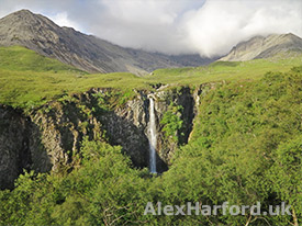 The spectacular Eas Mòr waterfall, with Skye's Cuillin clouded in the background