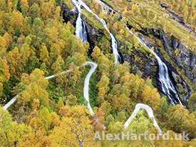 Winding steep road and waterfall in autumn
