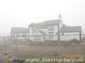 Fire-damaged Waggon & Horses pub on a misty morning