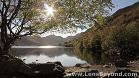 Llyn Crafnant Reservoir with sunburst through trees