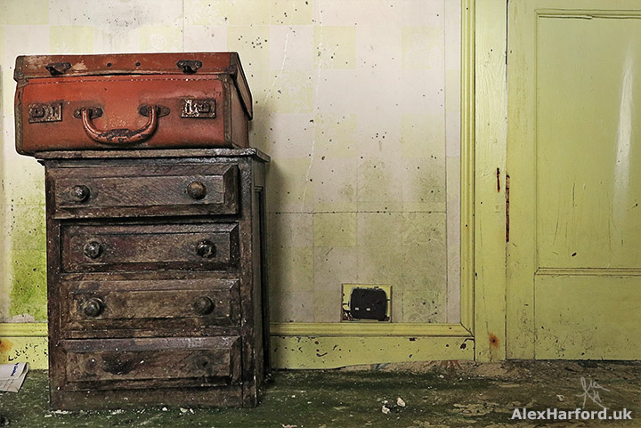 Old wooden chest of drawers topped by an old brown leather suitcase