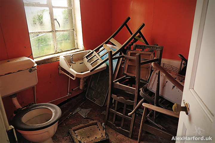 A pile of wooden chairs next to a sink and toilet