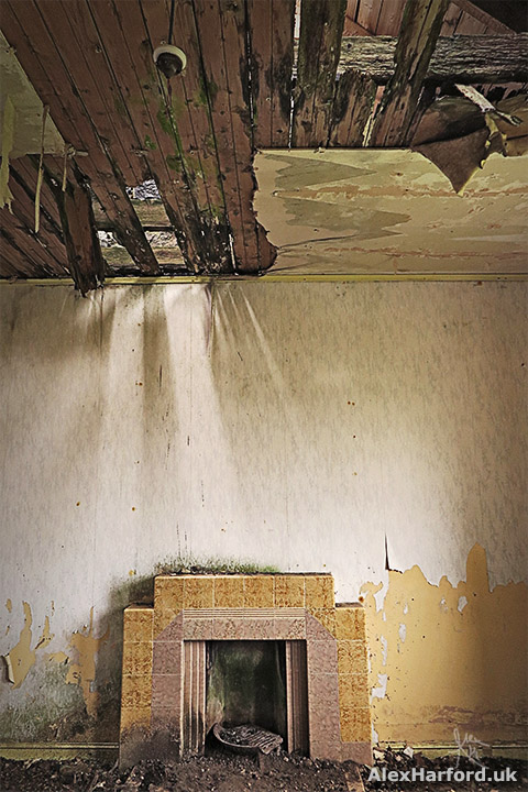 Yellow and beige-tiled fireplace below fallen floorboards