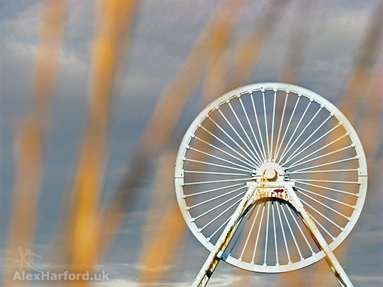 A sunlit Apedale pit wheel, through orange grass