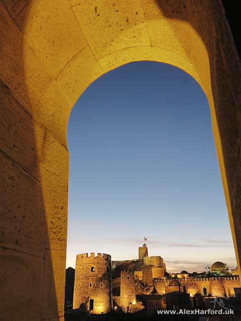 Rabati castle grounds through an arch at night