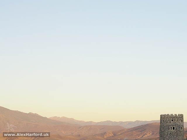 A brown desert-like landscape and castle turret