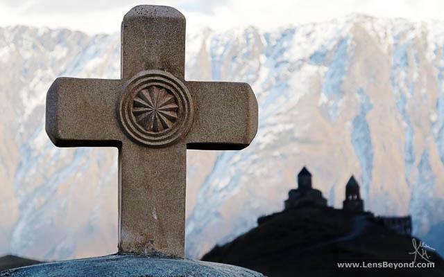 Cross and Gergeti Trinity Church in silhouette