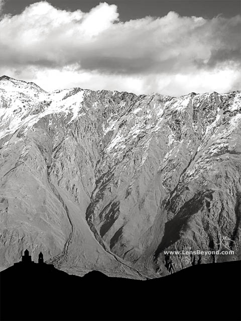 Black and white photo of Gergeti Trinity Church silhouetted against mountains