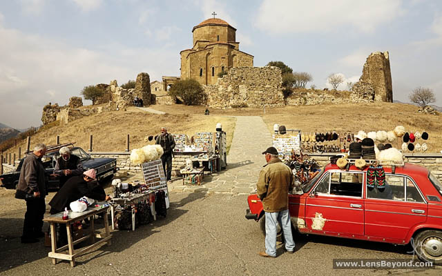 Souvenir sellers and their cars backed by Jvari Church