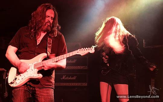 Bryan Josh playing guitar and Olivia Sparnenn dancing