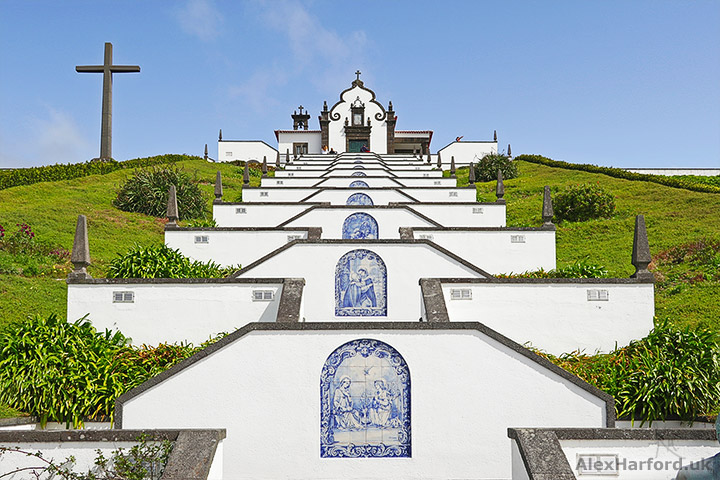 Steps to white chapel with blue sky and blue tiled scenes