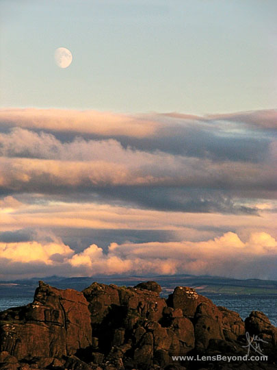 Moon and sunset with foreground rocks