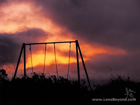 Sunset with children's swings silhouette