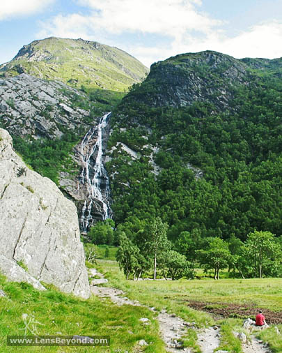 Steall Falls in background with large rock and person in foreground
