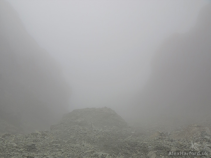 Great Stone Chute hidden in cloud, with mountain rocks rising either side