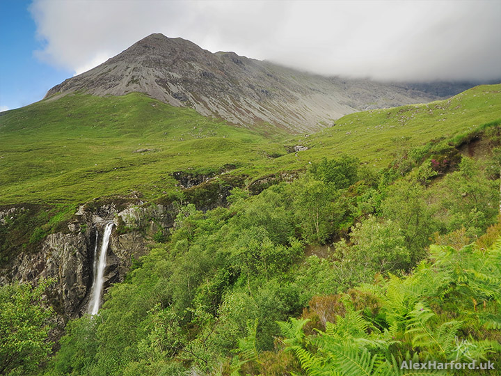 Eas Mòr with green ferns and trees backed by Sgùrr nan Gobhar