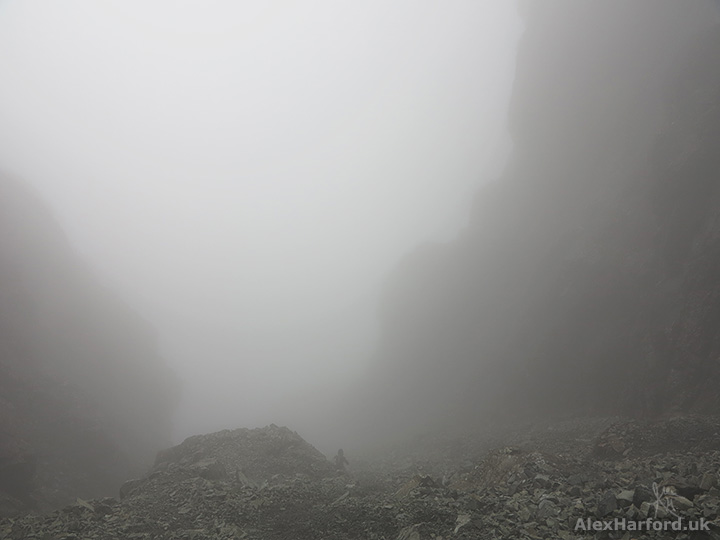 Top of cloud-hidden Great Stone Chute, with steep rocks rising either side
