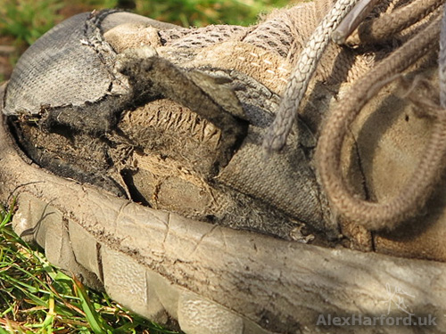 Walking shoes torn by scree