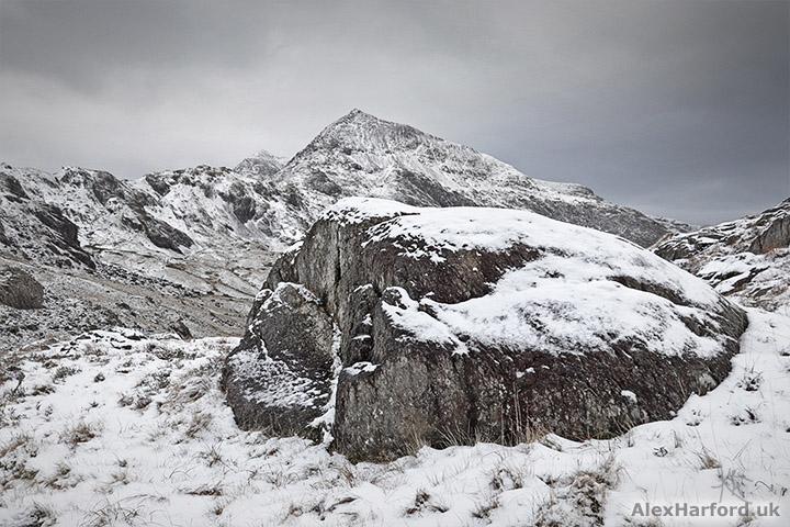 Snowy Snowdon-shaped rock backed by a snowy Snowdon