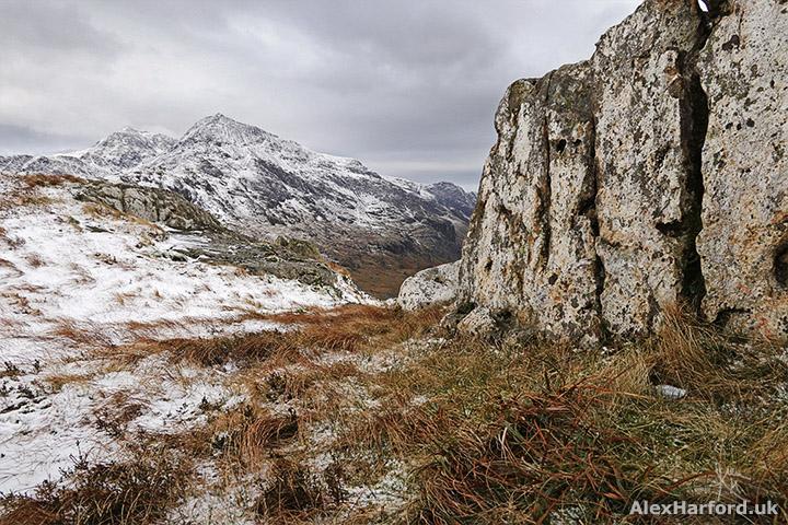 Snowy Snowdon from Moel Berfedd summit in shelter of rock